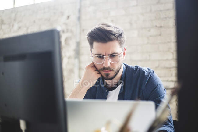 Male IT professional thinking while working on computer codes in laptop at workplace — Photo de stock