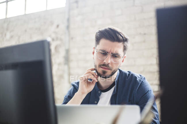 Thoughtful young IT expert touching beard while looking at laptop in office — Stock Photo