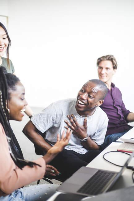 Des pirates informatiques joyeux discutent à leur bureau dans un bureau de création — Photo de stock