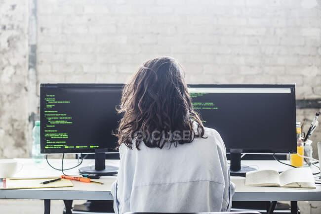 Rear view of female computer hacker coding at desk in creative office — Photo de stock