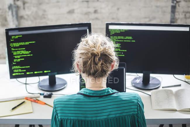 Vista ad alto angolo di esperto IT femminile che lavora su programmi per computer alla scrivania in ufficio creativo — Foto stock