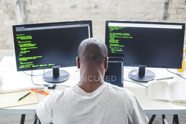 High angle view of shaved head computer programmer programming codes at desk in office — Photo de stock
