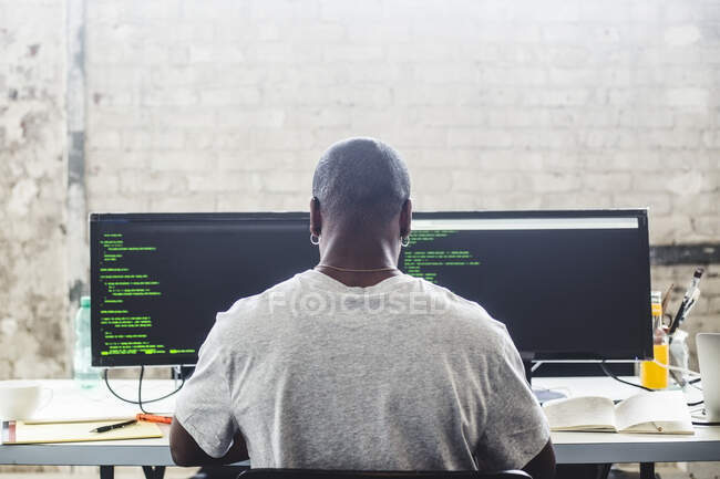 Rear view of male IT expert using computer while coding at creative workplace — Photo de stock