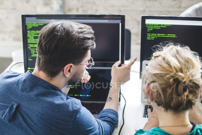 Professional hackers discussing over computer codes on monitor in creative office — Photo de stock