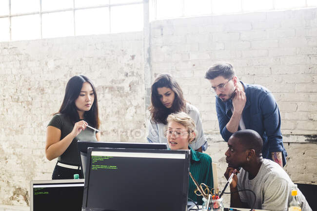 Confident young professionals planning while coding in computer at workplace — Photo de stock