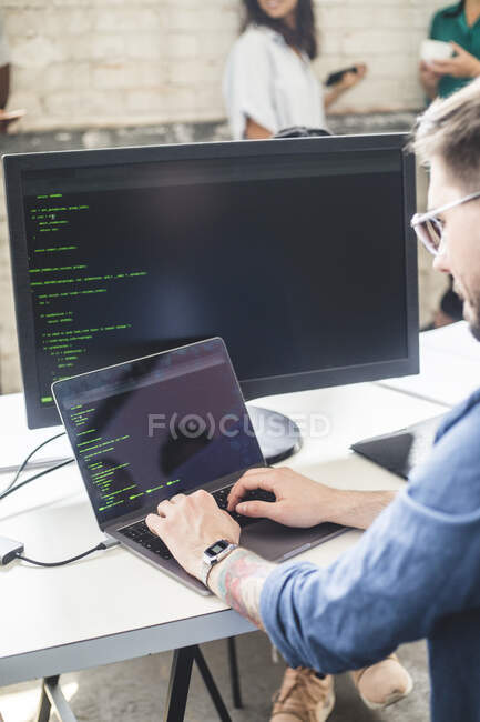 Male computer programmer coding in laptop while working at desk in office — Stock Photo