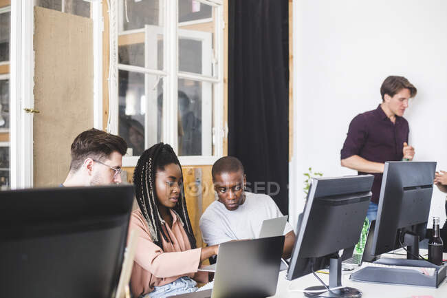 Team of confident young computer programmers working on new project in creative office — Photo de stock
