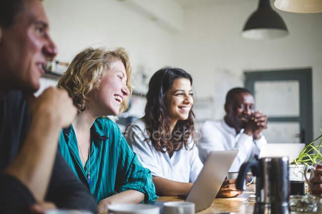 Sorridenti hacker professionisti che guardano lontano mentre si siede a tavola in start-up office — Foto stock