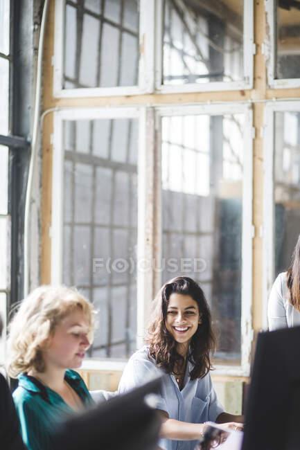 Sorridente programmatore di computer femminile guardando il collega mentre lavora in ufficio creativo — Foto stock