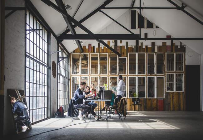 Réflexion d'hommes et de femmes d'affaires dans une salle de réunion lors d'une réunion sur un lieu de travail créatif — Photo de stock