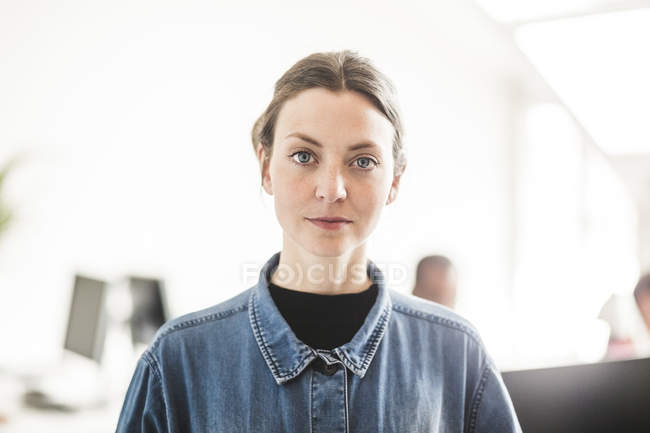 Portrait of confident businesswoman standing in creative office — Stock Photo