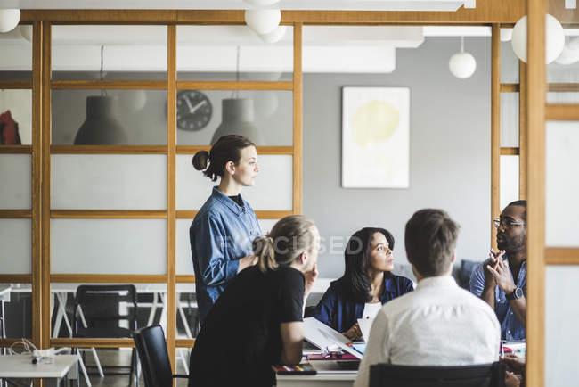 Des collègues masculins et féminins planifient une stratégie d'affaires dans un bureau de création — Photo de stock