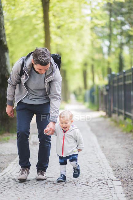 Longitud completa de padre e hijo tomados de la mano mientras caminan por el sendero - foto de stock