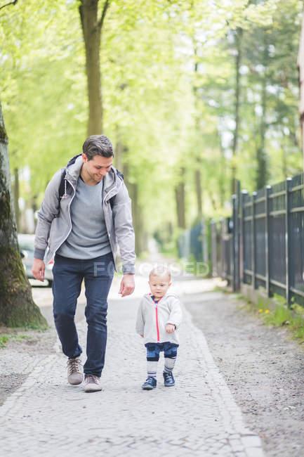 Longitud completa de padre sonriente mirando a su hijo caminando por el sendero - foto de stock