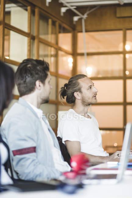Des collègues masculins discutant de plan d'affaires lors d'une réunion au conseil — Photo de stock