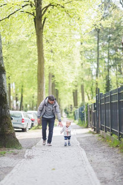 Comprimento total do pai com o filho andando no caminho — Fotografia de Stock
