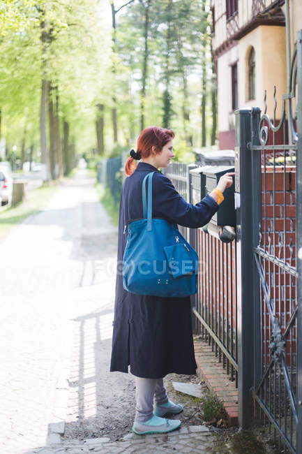 Full length of woman entering password on security system over gate — Stock Photo