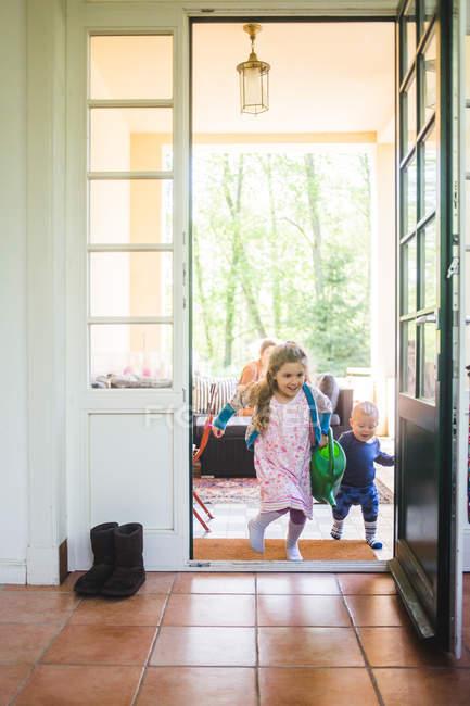 Full length of siblings running at entrance — Stock Photo