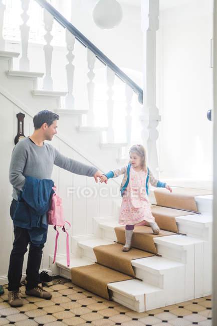 Повний батько тягне школярку за собою. — стокове фото