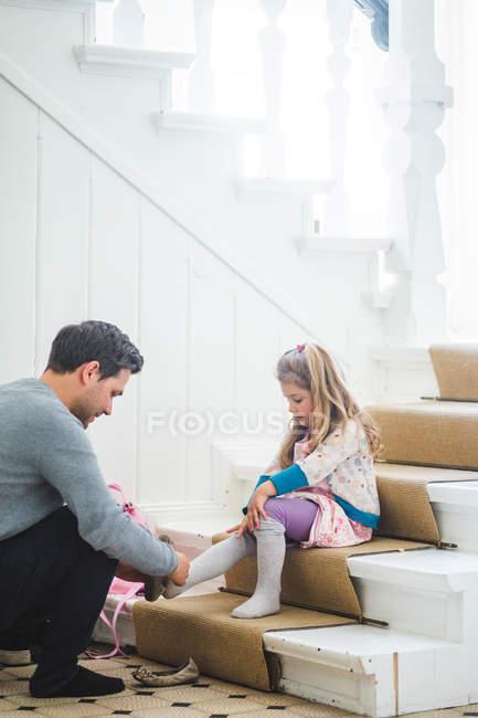 Батько допомагав школярці носити взуття, сидячи на сходинках удома. — стокове фото