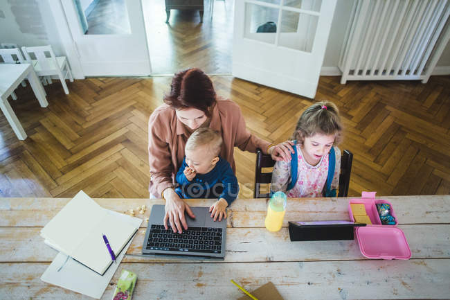 High angle view of mother working on laptop while sitting with cute son by daughter using digital tablet at table — Stock Photo