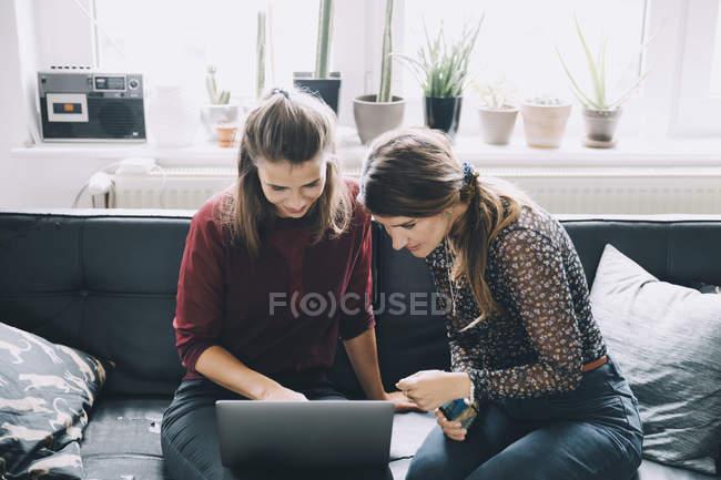 Высокоугольный вид коллег-женщин, обсуждающих за ноутбуком, сидя в творческом кабинете — стоковое фото