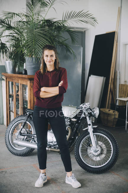 Portrait of confident female entrepreneur standing with arms crossed against motorcycle in creative office — Stock Photo
