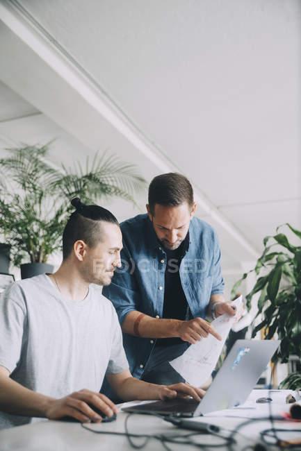 Empresários criativos discutindo sobre o documento na mesa no escritório — Fotografia de Stock