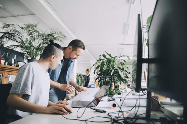 Empresários do sexo masculino discutindo sobre documento na mesa em escritório criativo — Fotografia de Stock
