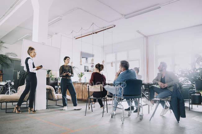 Бизнесменки обсуждают с коллегами творческий офис — стоковое фото