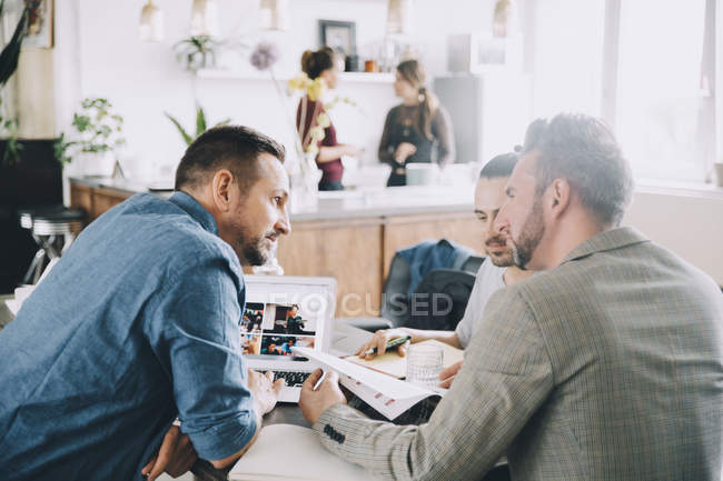 Empresarios masculinos creativos debatiendo en la mesa en el cargo - foto de stock