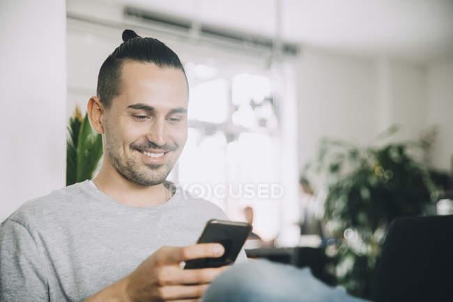 Un empresario creativo sonríe mientras utiliza un teléfono inteligente en su oficina. - foto de stock