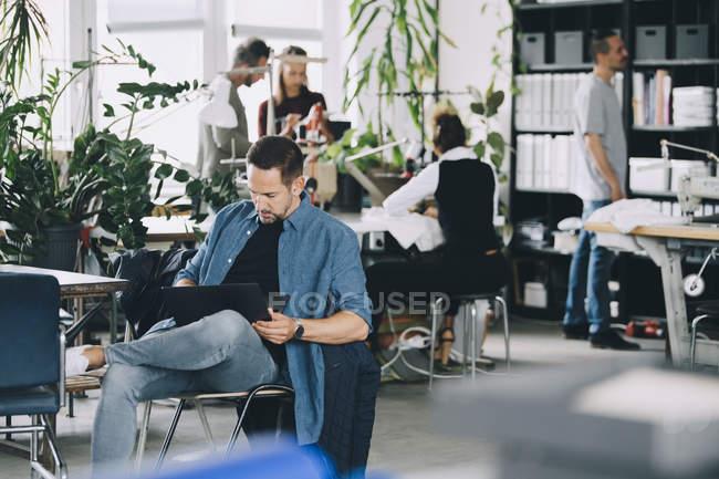 Uomo d'affari fiducioso che utilizza il computer portatile in ufficio creativo — Foto stock
