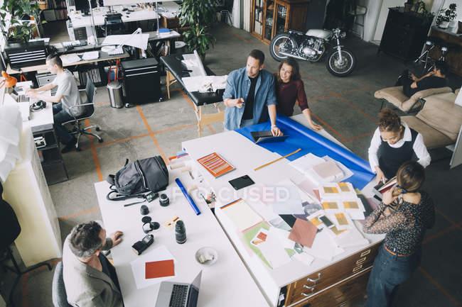 Вид на креативных бизнесменов и предпринимательниц, работающих за столом в офисе — стоковое фото