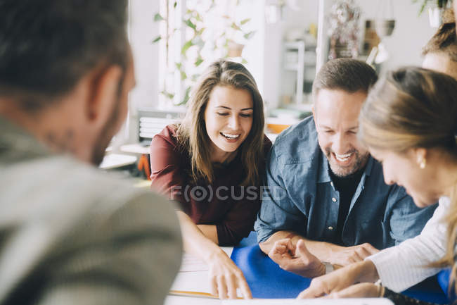 Cheerful male and female entrepreneurs at table during meeting in creative office — Stock Photo