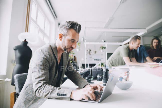 Уверенный бизнесмен использует ноутбук за столом в творческом офисе — стоковое фото