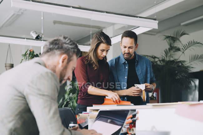 Бизнесмен и бизнесвумен обсуждают, пока коллега-мужчина работает над ноутбуком в творческом офисе — стоковое фото
