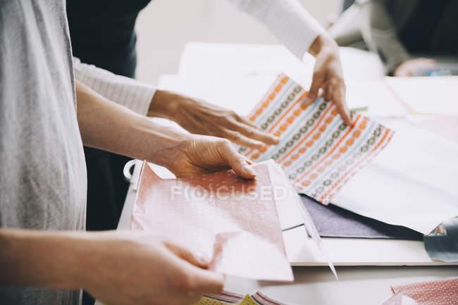 Руки деловых женщин с образцами за столом в офисе — стоковое фото