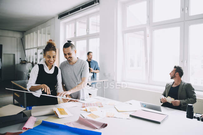 Smiling male and female professionals discussing at table in creative office — Stock Photo