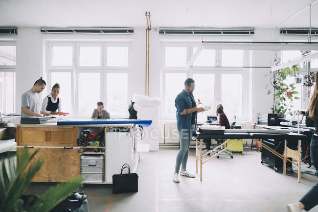 Profesionales multiétnicos de las empresas que trabajan en oficinas creativas - foto de stock