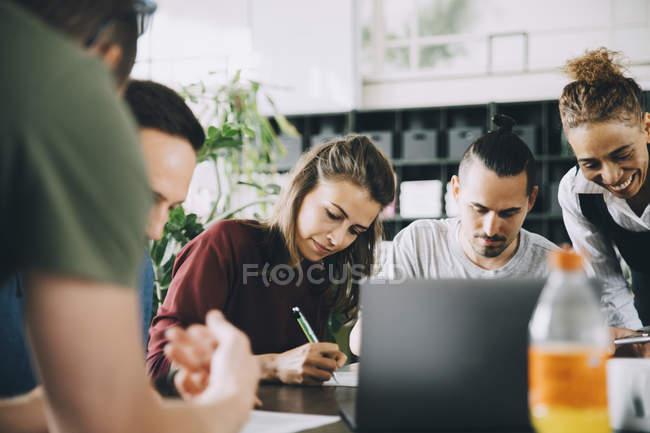 Многоэтнические мужчины и женщины-профессионалы, работающие за столом в творческом офисе — стоковое фото