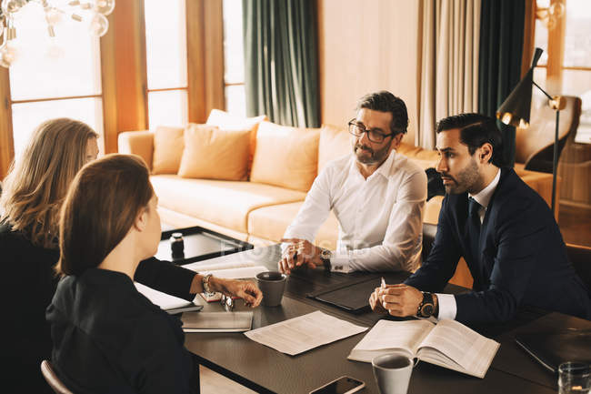 Male and female legal coworkers planning in meeting at board room — Stock Photo