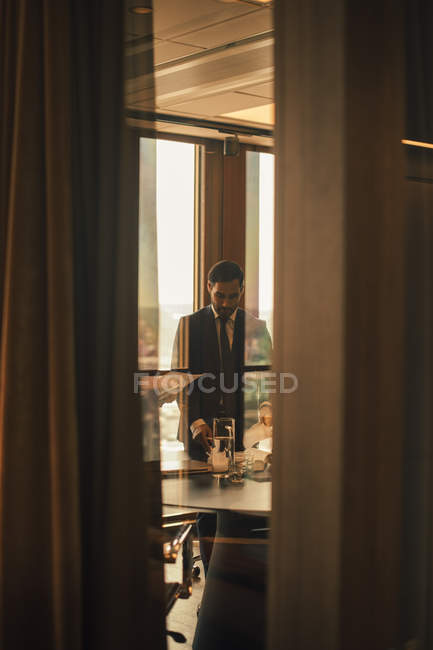 Mid adult lawyer reading book seen from doorway at law office — Stock Photo