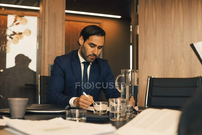 Serious male financial advisor reviewing documents at legal office — Stock Photo