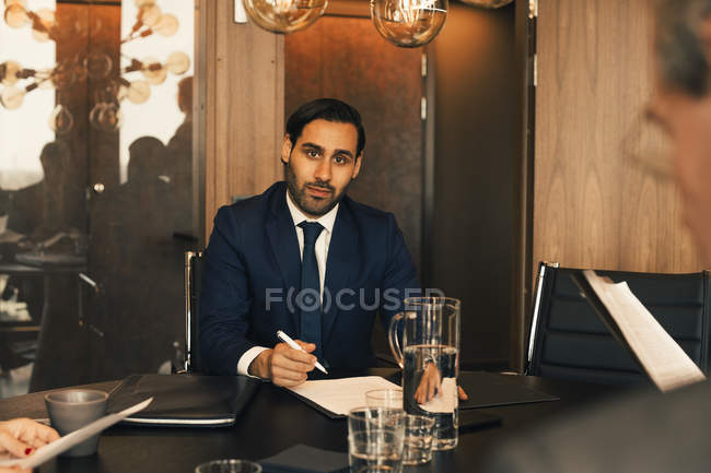 Portrait of confident mid adult lawyer with documents at conference table in law office — Stock Photo