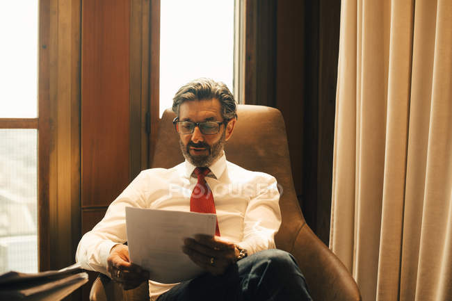 Asesor financiero masculino leyendo documentos en la oficina legal - foto de stock