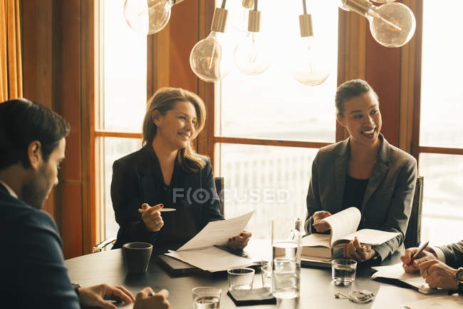 Smiling male and female legal professionals discussing on documents at meeting in office — Stock Photo