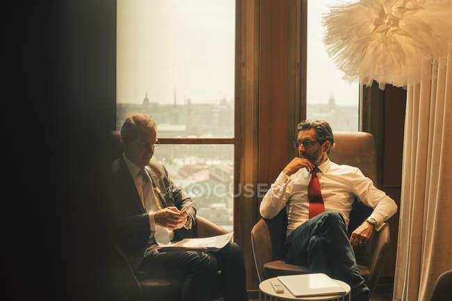 Conseillers financiers masculins discutant tout en étant assis contre la fenêtre au cabinet d'avocats — Photo de stock