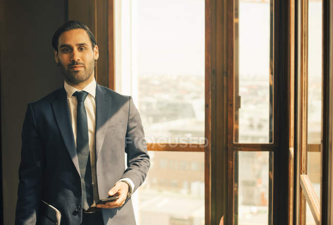 Portrait of confident male advisor standing by window at legal office — Stock Photo