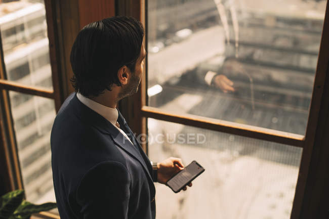 High angle view of thoughtful financial advisor texting on mobile phone by window at office — стокове фото
